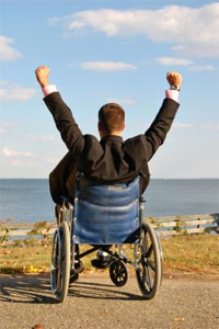 Workers' comp benefits: An injured worker in a wheelchair with hands up showing success and pride in achievement.